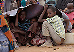 Somali refugee children take shelter from the sun as their family waits to be assigned a new tent in an extension of the world's largest refugee settlement. Swelled with tens of thousands of recent arrivals fleeing drought in Somalia, the Dadaab camp in northeastern Kenya has been unable to absorb the newest arrivals. The Lutheran World Federation, a member of the ACT Alliance, is manager of the camp and in July began moving hundreds of families into tents in the extension.
