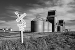 Rural environment with big grain stores beside railroad