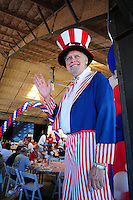 """Tempe, Arizona. October 13, 2012 - A man dressed as """"Uncle Sam"""" who was standing on stilts was one of the attractions of a colorful non-partisan political rally where hundreds of registered voters learned more about candidates the campaign process. Hundreds of Arizona registered voters participated in a political rally where candidates for the US Senate, House of Representatives, state legislature, Maricopa County and other public offices pitched for votes for the upcoming general election. Photo by Eduardo Barraza © 2012"""