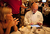 """Chef instructor and guest judge Eric Gephart registers himself in the """"voter's portal"""" prior to the start of the competition dining event. Once registered, diners were instructed to vote on each course using a scale of 1 to 5 in categories including aroma, presentation, taste and use of the secret ingredient. The event is styled after the popular Iron Chef television series, except that a room full of diners are weighted 70% of the vote and the guest judges are weighted the remaining 30% in determining a winner."""