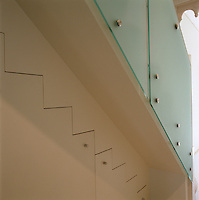 The built-in understairs cupboard follows the lines of the staircase which is clad in opaque glass