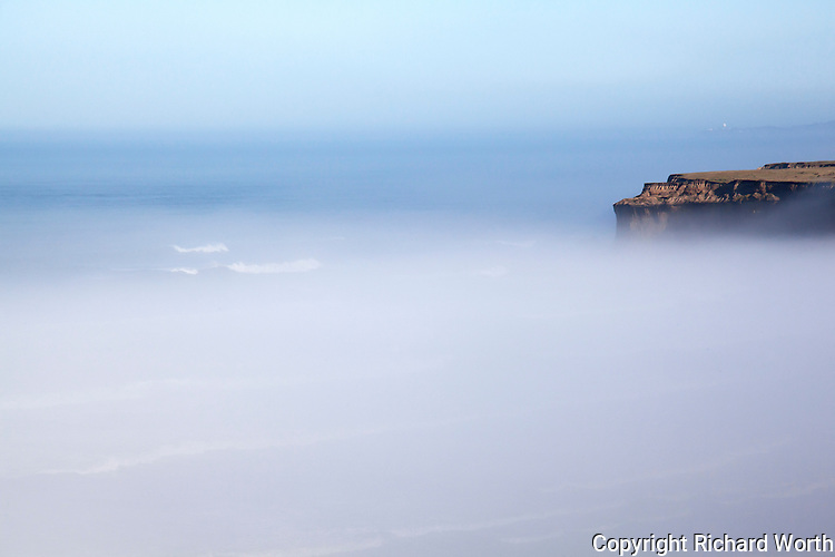 A slice of jagged coastal bluff juts out above the fog blanketing, enveloping,  the coast off Highway 1 south of Half Moon Bay.  On the horizon, eleven and a half miles away and barely visible, is the round radar orb at Pillar Point above Mavericks, infamous among surfers.