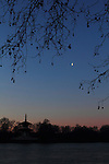 Dawn over Battersea Park, London, on a clear January day with a waning crescent moon visible - with the Buddhist temple on the left.