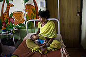 25 year old mother, Sushma is seen with her 11 month malnutritioned daughter, Shilpi at the 'Nutritional Reahabilitation Centre' at the pediatrics section of Maharani Laxmibai Medical College in Jhansi, Uttar Pradesh, India. The Indian government spends $1.4 billion a year - on programs that include weighing newborn babies, counseling mothers on healthy eating and supplementing meals, but none of this is yeilding results. According to UNICEF, some 48% of Indian children, or 61 million kids, remain malnourished, the clinical condition of being so undernourished that their physical and mental growth are stunted. Photo: Sanjit Das/Panos for The Wall Street Journal.Slug: IMALNUT