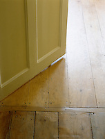 Detail of the bottom of an open painted wooden door and two different types of wooden floorboards.