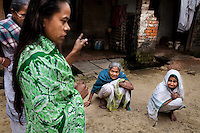 """(L-R: Purnima Mandol, 36, in green; Saraswati Saha, 84, blue shawl; and Kamla Das, 90, white sari) Refugees of The Partition gather and discuss their unfortunate situation outside their homes in Cooper's Camp, Nadia district, Ranaghat, North 24 Parganas, West Bengal, India, on 19th January, 2012. """"I was born here, but I spent my entire life growing up as a refugee. I grew up standing in line for government handouts."""" says Purnima angrily. Over 60 years after the bloody creation of Bangladesh in 1947, refugees who fled what was then known as West Pakistan to India still live as refugees. .Photo by Suzanne Lee for The National (online byline: Photo by Szu for The National)"""