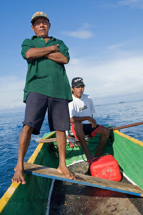 """Two Kuna Yala men on a Cayuko """"dug-out canoe"""" transport locals and visitors through the San Blas Islands, Panama"""