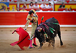 Spanish matador David Mora performs a pass with capote to a El Pilar bull during the fourth corrida of the San Fermin Festival, on July 10, 2012, in the Northern Spanish city of Pamplona. (c) Pedro ARMESTRE