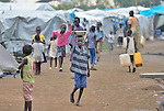 A boy walks along a street in a camp for internally displaced families located inside a United Nations base in Juba, South Sudan. The camp holds Nuer families who took refuge there in December 2013 after a political dispute within the country's ruling party quickly fractured the young nation along ethnic and tribal lines. The ACT Alliance is providing a variety of services, including fresh water, to the more than 20,000 people living in the camp.