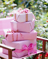 A pile of presents wrapped in pink paper and ribbon on a chair in the garden