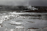 Tourists wander along pathways between the steamy geothermal pools at Geysir, South-West Iceland