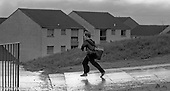 Running through the rain, Wester Hailes, Scotland, 1979.  John Walmsley was Photographer in Residence at the Education Centre for three weeks in 1979.  The Education Centre was, at the time, Scotland's largest purpose built community High School open all day every day for all ages from primary to adults.  The town of Wester Hailes, a few miles to the south west of Edinburgh, was built in the early 1970s mostly of blocks of flats and high rises.