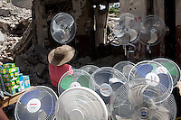 A woman arranges fans in her market stall on July 8, 2010 in Port-au-Prince, Haiti.