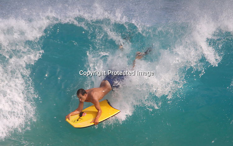 A board drops in to a good wave at Sandy Beach in Hawaii.