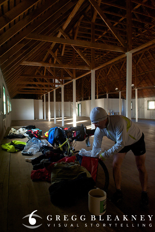 gMack sorts his cycling gear after spending the night in the largest timber frame barn west of the Mississippi - Springville Ranch - Springville, CA - Adventure Cycling Sierra Cascades Route - Canada to Mexico Cycling Expedition