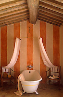 The shower curtains are draped over a pair of stripped wooden armchairs which stand on either side of the roll-topped bath in this red and white striped bathroom