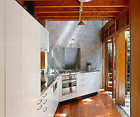 The kitchen units, which define one side of the open-plan living space, follow the line of the angled wall