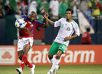 Costa Rica's Froylan Ledezma (21) hits a shot past Mexican goalkeeper Guillermo Ochoa (1, not pictured) at the end of stoppage time in the second half to tie the game 1-1 as Mexico's Juan Carlos Valenzuela (21) looks on.  Mexico defeated Costa Rica 2-1 on penalty kicks in the semifinals of the Gold Cup at Soldier Field in Chicago, IL on July 23, 2009.