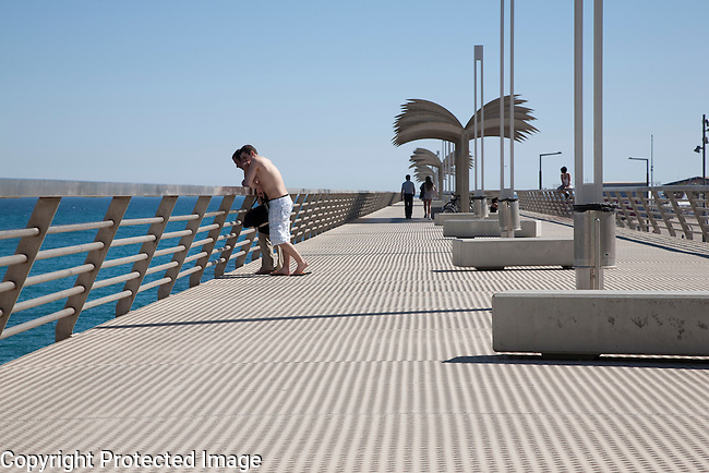 Two men looking out to sea Alicante city harbour wall Pier Promenade walk