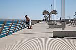 Two men looking out to sea Alicante city harbour wall Pier Promenade walk