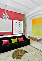 A contemporary living room with barrel ceiling. The room is white with vibrant accent colours. A black sofa provides a strong colour contrast against a pink wall.