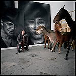 Zhang Dali with stuffed Mongolian horses and examples of his AK47 painting series at his studio on the outskirts of Beijing, China.