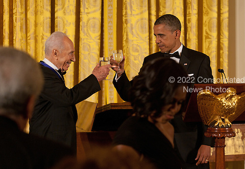 United States President Barack Obama offers a toast to President Shimon Peres of Israel following his being awarded the Presidential Medal of Freedom during a dinner in his honor in the East Room of the White House in Washington, D.C. on Wednesday, June 13, 2012..Credit: Martin Simon / Pool via CNP