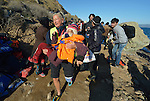 Lisbeth Svendsen, a volunteer from Norway, carries a refugee child as she and other volunteers welcome a boat load of refugees to a beach near Molyvos, on the Greek island of Lesbos, on November 2, 2015. The refugees were on a boat that traveled to Lesbos from Turkey, provided by Turkish traffickers to whom the refugees paid huge sums. Svendsen is one of hundreds of volunteers on the island who receive the refugees and provide them with warm clothing and medical care before they continue their journey toward western Europe.
