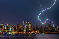 A large cloud to ground forked lightning bolt strikes the ground in New York City during a summer thunderstorm on Thursday, July 26, 2012.
