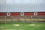 Three windows framed in white on a red barn with rustic fence and green pasture.
