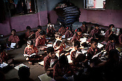 Students attend their classes in a government run school in Caregaon, Thane, Maharashtra. Students from lower income group families attend the class during the day and later at night sleep in the same classroom. These schools run a specially designed concept of 'aflatoon' as part of the curriculam whereby students are made aware of their child as described in the convention of rights of child. These students are made aware of right to survival, right to protection, right to development and right to participation.