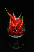Hot bright red chilli peppers filling brandy glass to portray a hot drink
