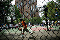 12 June 2006 - New York City, NY - A boy passes behind the court where tryouts for the Rucker's street basketball tournament are taking place at Rucker Park in Harlem, New York City, USA, Sunday June 12 2005. Photo Credit: David Brabyn