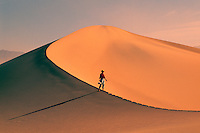 Death Valley National Park, California, CA, USA - Woman walking on Mesquite Sand Dune near Stovepipe Wells at Sunrise (Model Released)