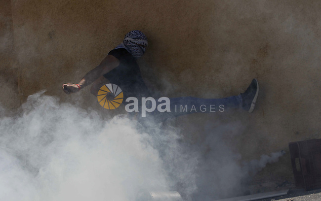 Palestinians youths stand amid tear gas smoke during clashes with Israeli security forces on April 25, 2015 in Al-Tur neighbourhood of annexed Arab east Jerusalem, after Israeli police shot dead a knife-wielding Palestinian who attempted to stab colleagues at an east Jerusalem checkpoint. The 17-year-old assailant from Al-Tur managed to get past one checkpoint but was brought down at a second near Al-Zaim without any police casualties, a spokeswoman said. Photo by Saeb Awad