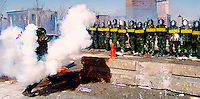 A protester throws a tear gas cannister back at a line of riot police on the first day of rioting at the Summit of the Americas in Quebec City April 20.<br />