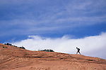 Hiker crossing slickrock, Grand Staircase-Escalante National Monument, Utah