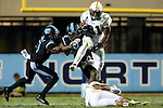 18 October 2014: Georgia Tech's Charles Perkins (21) is tackled by UNC's Norkeithus Otis (8) and Sam Smiley (3). The University of North Carolina Tar Heels hosted the Georgia Tech Yellow Jackets at Kenan Memorial Stadium in Chapel Hill, North Carolina in a 2014 NCAA Division I College Football game. UNC won the game 48-43.