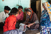 Kamlesh Kumari (2nd from right), 28, reads this week's Khabar Lahariya newspaper out loud to her whole family and illiterate friends at her house in a village in Chitrakoot, Uttar Pradesh, India on 5th December 2012. Kamlesh, a mother of 2, is a farmer, earning about 20000 rupees of sales per annum from her 2 acre farm. She dreams of becoming a journalist for Khabar Lahariya but is not able to apply since the newspaper only takes one reporter in each area, and Sunita is already working in the area. Photo by Suzanne Lee for Marie Claire France.