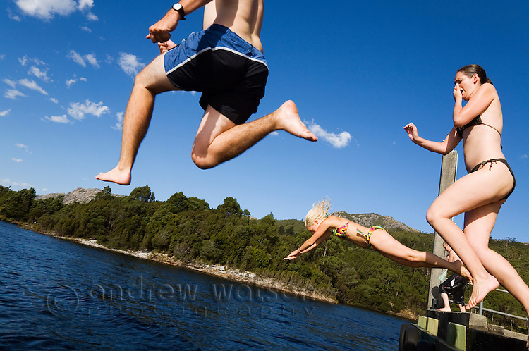 A group of young men and women take a leap into a lake to cool off.  Lake Rosebery, Tullah, Tasmania, AUSTRALIA