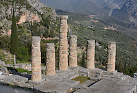 DELPHI, GREECE - APRIL 10 : A focused view of the 6 remaining Doric columns of the peristasis of the Temple of Apollo overlooking the slopes of the Mont Parnassus with a miniature view of the Tholos in the distance, on April 10, 2007 in the Sanctuary of Apollo, Delphi, Greece. The ruins of the Temple of Apollo belong to the 4th century BC, the third temple built on the site and completed in 330BC. Its architects were the Corinthians Spintharos Xenodoros and Agathon. (Photo by Manuel Cohen)