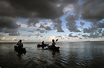 3 kayakers silouetted against the early evening sky in the waters of Florida Bay off Flamingo in Everglades National Park.