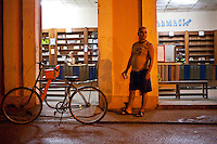 L'Avana, signore con bicicletta davanti a una farmacia, notturno