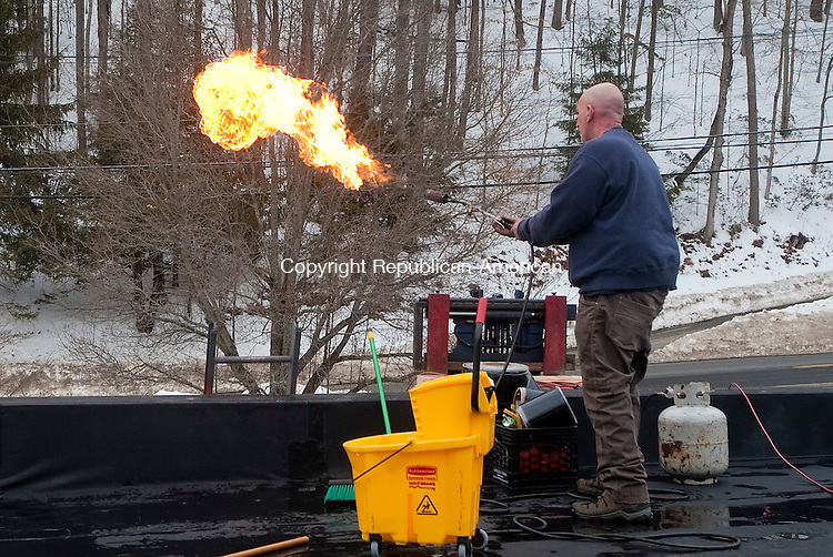 NORFOLK, CT-022014JS04- Rob Paolino of Paolino Roofing in Waterbury, readies a propane heating torch prior to patching cuts in the rubber roof at New England Miniature Ball in Norfolk on Thursday. The crew that cleared snow off the roof used metal edge shovels that left a number of cuts in the roof causing the roof to leak. <br /> Jim Shannon Republican-American