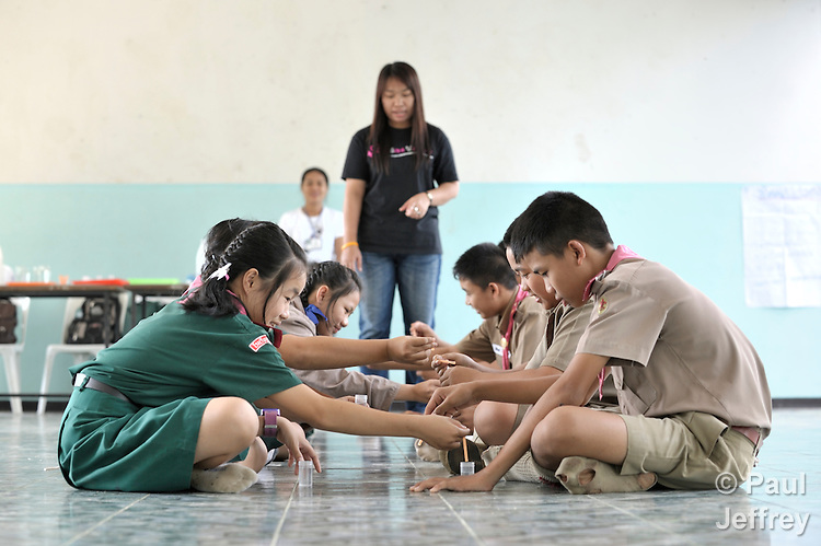"""Wearing their scouting uniforms, children in the village of Toong-sa-tok in northern Thailand learn about HIV and AIDS during a session at the temple-supported Banhuarin School. Helping teach the class is Srisangwan Punyapeng, an HIV positive woman who works with Jai-Kao-Jai-Rao (the """"Let's Talk About HIV"""" Association). Here she helps children conduct an experiment where they mix fluids in test vials to show how diseases can be passed from one person to another."""