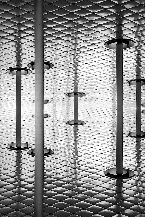 The abstract photograph of the underside of a mirrored canopy with a distinctive trim and columns.