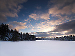 Covered with snow frozen lake sunset winter landscape nature scenery at Algonquin Provincial Park, Ontario, Canada