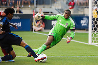 Goalkeeper Sean Johnson (25) of the Chicago Fire makes a stop on Sheanon Williams (25) of the Philadelphia Union. The Chicago Fire defeated the Philadelphia Union 3-1 during a Major League Soccer (MLS) match at PPL Park in Chester, PA, on August 12, 2012.