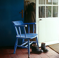 A blue painted kitchen chair and a pair of discarded boots by the open back door