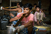 A child is working in a small-scale glass industry in the slum surrounding Firozabad, renowned as the 'glass city', in Uttar Pradesh, northern India. The air is filled with ammoniac and other chemicals making it hard even to breathe for only a few minutes before feeling dizzy and disorientated. The boy's co-workers, a few years older than him, are breathing in the ammoniac through glass pipes that once broken into small pieces will be attached to dresses as glittering decorations. Due to extreme poverty, over 20.000 young children are employed to complete the bracelets produced in the industrial units. This area is considered to be one of the highest concentrations of child labour on the planet. Forced to work to support their disadvantaged families, children as young as five are paid between 30-40 Indian Rupees (approx. 0.50 EUR) for eight or more hours of work daily. Most of these children are not able to receive an education and are easily prey of the labour-poverty cycle which has already enslaved their families to a life of exploitation. Children have to sit in crouched positions, use solvents, glues, kerosene and various other dangerous materials while breathing toxic fumes and spending most time of the day in dark, harmful environments. As for India's Child Labour Act of 1986, children under 14 are banned from working in industries deemed 'hazardous' but the rules are widely flouted, and prosecutions, when they happen at all, get bogged down in courts for lengthy periods. A ban on child labour without creating alternative opportunities for the local population is the central problem to the Indian Government's approach to the social issue affecting over 50 million children nationwide.